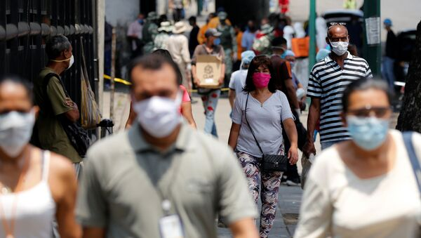 People wearing protective masks walk on a street during a nationwide quarantine as the spread of the coronavirus disease (COVID-19) continues, in Caracas, Venezuela April 20, 2020. - Sputnik International