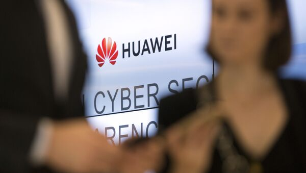 Two people look at their cellphones in front of the Huawei logo during a DigitALL lunch talk in Brussels, Tuesday, May 21, 2019 - Sputnik International