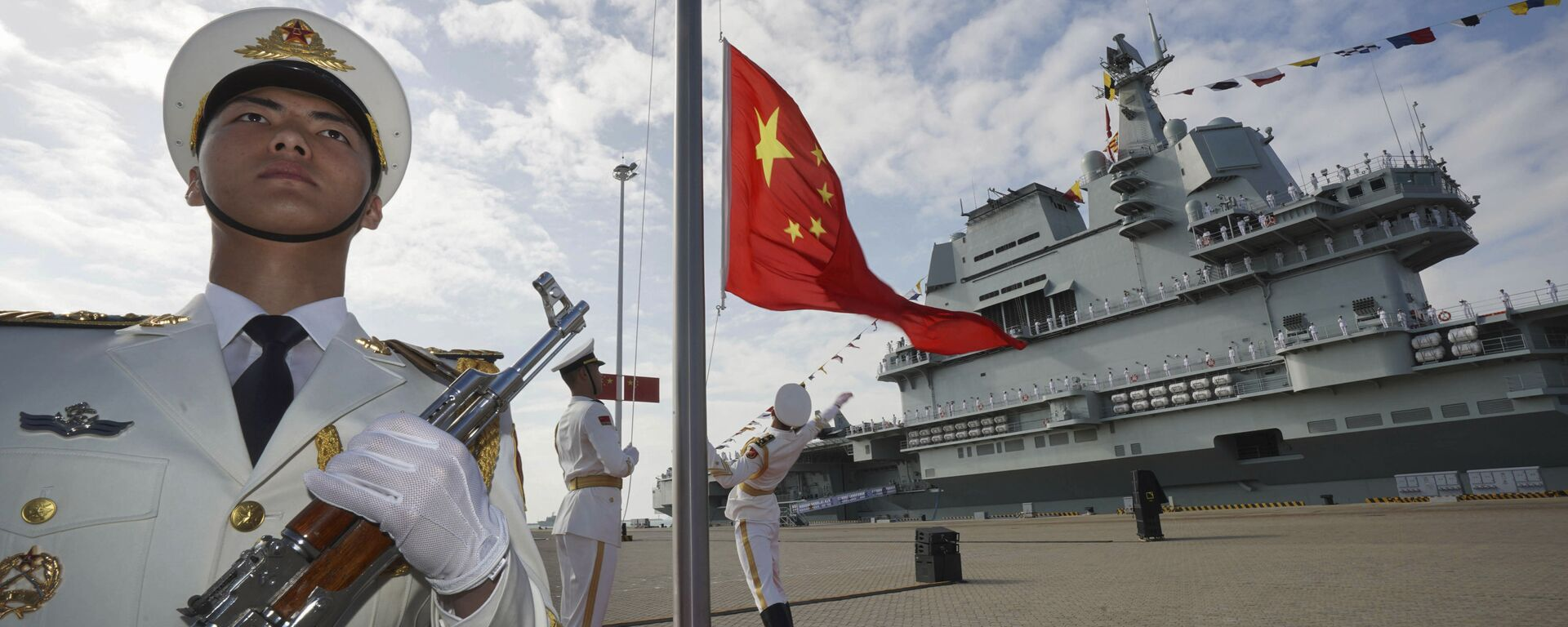 In this photo taken Dec. 17, 2019 and released Dec. 27, 2019 by Xinhua News Agency, Chinese honor guard raise the Chinese flag during the commissioning ceremony of China's Shandong aircraft carrier at a naval port in Sanya, south China's Hainan Province - Sputnik International, 1920, 16.09.2021