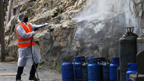 Palestinian worker sprays disinfectant as a preventive measure to help contain the coronavirus, in the West Bank city of Nablus, Wednesday, April 8, 2020.  - Sputnik International