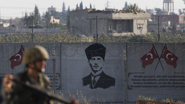 A Turkish soldier walks past Kemal Ataturk graffiti on a wall at the Syrian border - Sputnik International