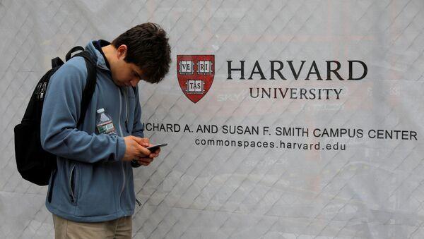 A man looks at his mobile phone beside a sign for Harvard University in Cambridge, Massachusetts, U.S., June 18, 2018. - Sputnik International