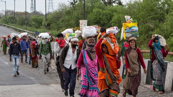 Friends and relatives of Kushwaha family who work as migrant workers walk along a road to return to their villages, during a 21-day nationwide lockdown to limit the spreading of coronavirus, in New Delhi, India, March 26, 2020 - Sputnik International
