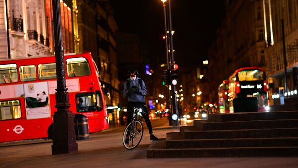 A delivery cyclist checks his phone in Piccadilly Circus during the late evening, as the city at night is deserted like never before while the coronavirus disease (COVID-19) lockdown continues, in London, Britain April 21, 2020 - Sputnik International