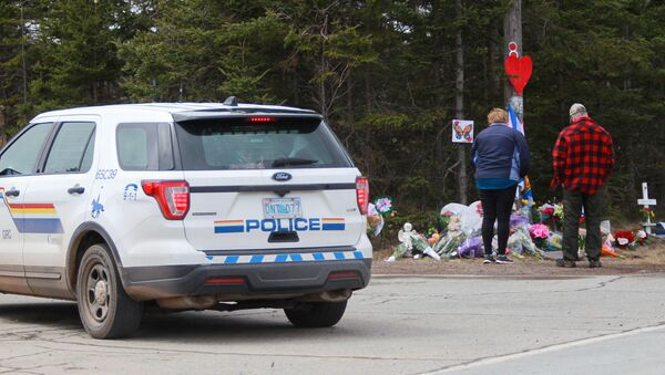 Mourners pay their respects in front of the makeshift memorial, made in the memory for the victims of Sunday's mass shooting as a Royal Canadian Police Vehicle passes nearby in Portapique, Nova Scotia, Canada April 23, 2020 - Sputnik International