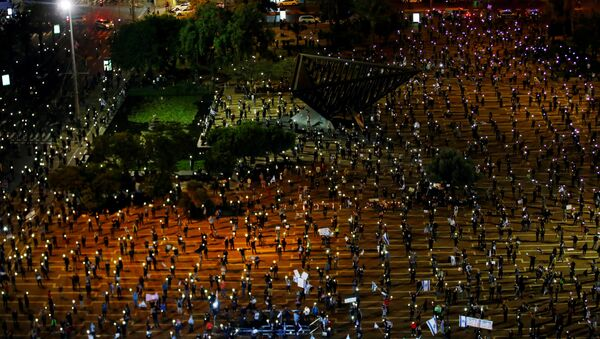 Israelis hold up their mobile phones as they demonstrate against Israel's Prime Minister Benjamin Netanyahu, under strict restrictions made to slow down the coronavirus disease (COVID-19) spread, on Rabin Square in Tel Aviv, Israel 19 April 2020 - Sputnik International