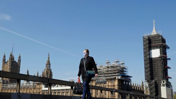 A woman wearing a face mask walks across Westminster Bridge with Big Ben clock and the Houses of Parliament in the background, as the spread of the coronavirus disease (COVID-19) continues, in London, Britain, April 23, 2020. REUTERS/John Sibley - Sputnik International