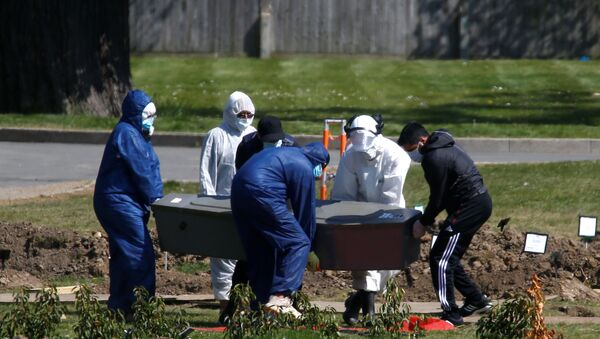 Workers wearing protective suits carry the coffin containing the body of a person at the Muslim cemetery Eternal Gardens in Kemnal Park Cemetery in Chislehurst, as the spread of the coronavirus disease (COVID-19) continues, London, Britain April 23, 2020. - Sputnik International
