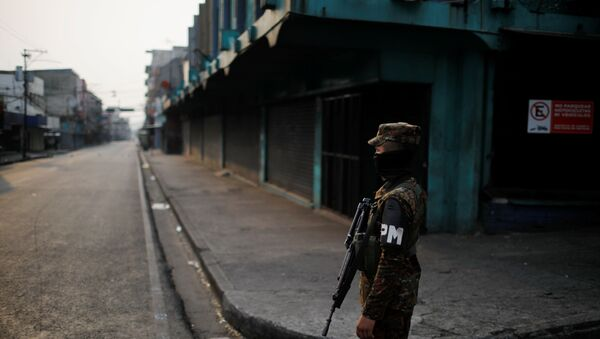 A military police officer stands close to a checkpoint during a police and army joint operation as part of security measures to keep people out of the city downtown markets during a quarantine throughout the country to curb the spread of the coronavirus disease (COVID-19), in San Salvador, El Salvador April 22, 2020. - Sputnik International