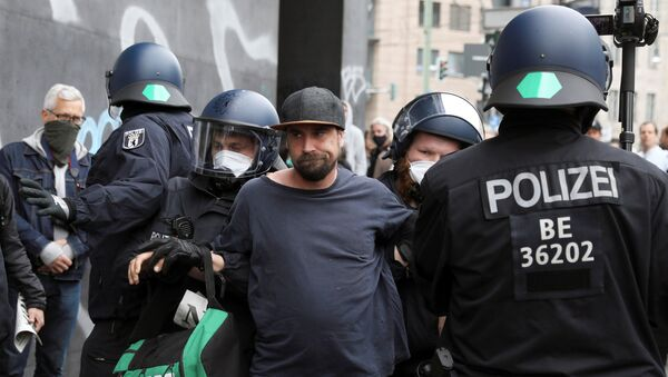 Police detain a protester during a demonstration against the lockdown imposed to slow down the spread of the coronavirus disease (COVID-19), in Berlin, Germany April 25, 2020. - Sputnik International