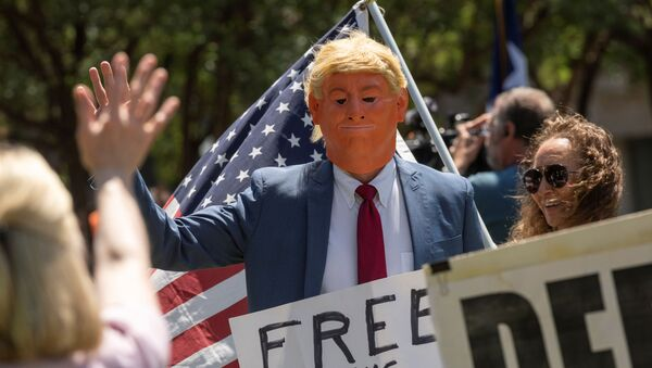 An attendee with a mask dressed to impersonate President Donald Trump walks through the crowd and waves at supporters as a group called Open Texas rally to re-open Texas businesses, places of work and religious services shut down by coronavirus (COVID-19) pandemic restrictions as they gather in a park outside of the City Hall in Frisco, Texas, U.S., April 25, 2020.  - Sputnik International