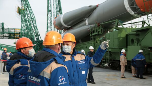 Specialists wearing protective face masks talk near the Soyuz MS-16 spacecraft for the next International Space Station (ISS) crew formed of Chris Cassidy of NASA, Anatoly Ivanishin and Ivan Vagner of the Russian space agency Roscosmos, which is prepared to be set at the launchpad ahead of its upcoming launch at the Baikonur Cosmodrome, Kazakhstan April 6, 2020. - Sputnik International