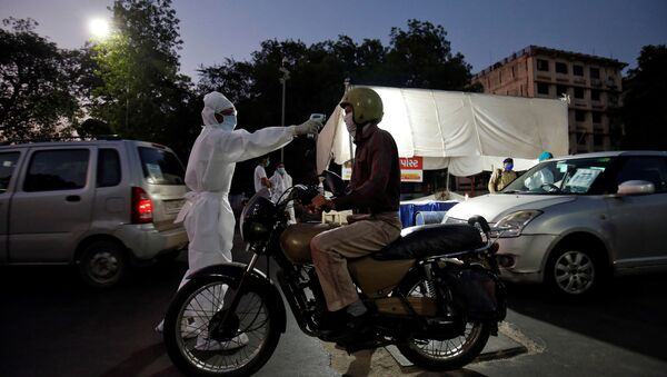 A health worker uses an infrared thermometer to measure the temperature of a motorcyclist on a road in India - Sputnik International