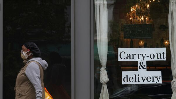 A pedestrian walks past a restaurant advertising their carry-out and delivery options during the outbreak of the coronavirus disease (COVID-19) in Washington, U.S., April 27, 2020 - Sputnik International