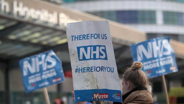 NHS signs are seen outside Queen Elizabeth Hospital during the Clap for our Carers campaign in support of the NHS, as the spread of the coronavirus disease (COVID-19) continues, in Birmingham, Britain, April 23, 2020.  - Sputnik International