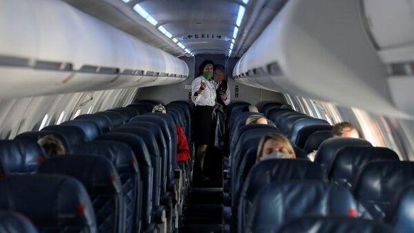 Flight attendants talk in a nearly empty cabin on a Delta Airlines flight operated by SkyWest Airlines as travel has cutback, amid concerns of the coronavirus disease (COVID-19), during a flight departing from Salt Lake City, Utah, U.S. April 11, 2020. - Sputnik International