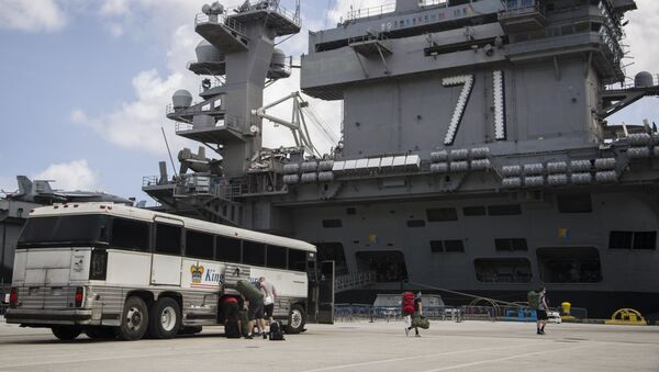 Sailors assigned to the aircraft carrier USS Theodore Roosevelt (CVN 71) prepare to embark the ship after weeks of cleaning and essential watch standing - Sputnik International