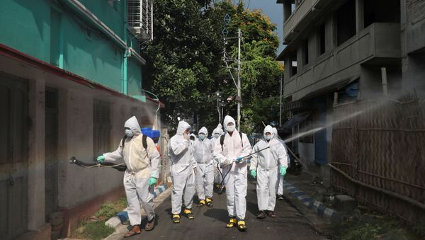 The spread of the coronavirus disease (COVID-19) in Kolkata Municipal workers wearing protective gear spray disinfectant in a residential area during a nationwide lockdown to slow the spreading of the coronavirus disease (COVID-19), in Kolkata, India, April 29, 2020.  - Sputnik International