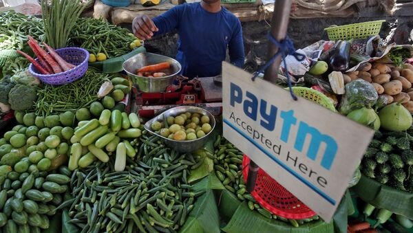 FILE PHOTO: A vendor weighs vegetable next to an advertisement of Paytm, a digital payments firm, hanging amidst his vegetables at a roadside market in Mumbai, India, April 2, 2019 - Sputnik International