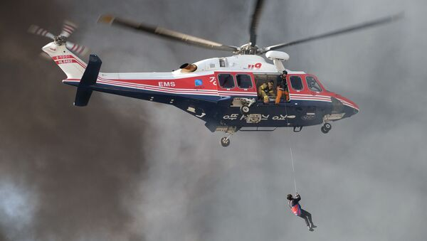 A resident (bottom) is surrounded by smoke as he is winched up to a rescue helicopter from an apartment building which caught fire in Uijeongbu, north of Seoul, on January 10, 2015 - Sputnik International