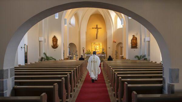 A Catholic priest celebrates a mass in the empty Church of Saint Catherine in Ralbitz, eastern Germany, Sunday, 12 April 2020.  - Sputnik International