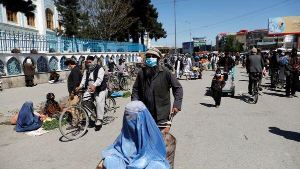 An Afghan woman sits in a handcart - Sputnik International