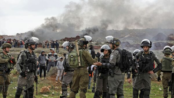 Israeli soldiers and borderguards stand guard during a Palestinian demonstration against Israeli settlements in the village of Qusra, in the Israeli occupied West Bank on March 2, 2020. - Sputnik International