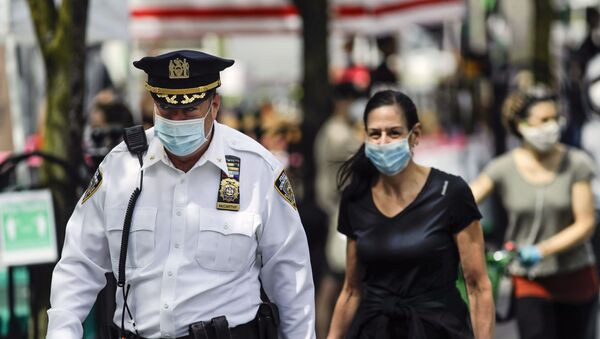 A police officer wears a protective mask as he walks among people at the Union Square GreenMarket Saturday, May 2, 2020, in New York - Sputnik International