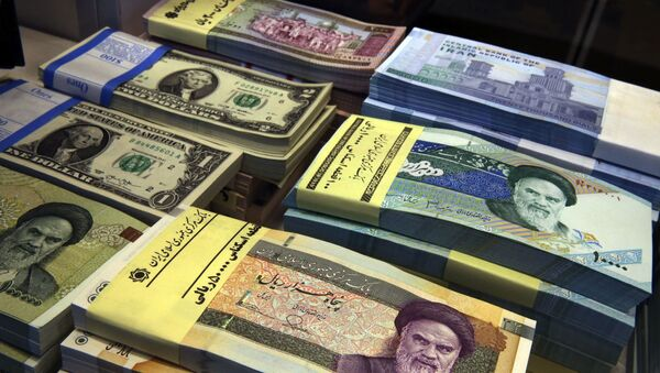 In this April 4, 2015 file photo, Iranian and U.S. banknotes are on display at a currency exchange shop in downtown Tehran, Iran. Iran's president has sent a bill to parliament that would cut four zeroes from value of the nation's sanctions-battered currency, the rial. Semi-official news agencies reported the news on Wednesday, Aug. 21, 2019, saying President Hassan Rouhani sent the bill with urgency to the parliament to consider. Iran's rial has been hammered by the effects of increasing U.S. sanctions on the country. - Sputnik International