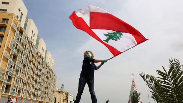 An anti-government demonstrator holds a Lebanese flag as she stands on top of her car, during a countrywide lockdown to combat the spread of the coronavirus disease (COVID-19), in Beirut, Lebanon April 21, 2020.  - Sputnik International