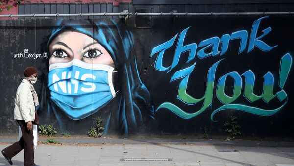A person wearing a protective face mask walks past the 'NHS Dedication Mural' by The Artful Dodger (A.Dee) in Elephant & Castle, following the outbreak of the coronavirus disease (COVID-19), London, Britain, 5 May 2020 - Sputnik International