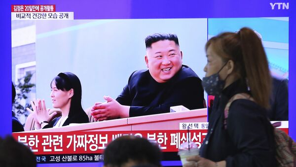 A woman passes by a TV screen showing an image of North Korean leader Kim Jong Un and his sister Kim Yo Jong during a news program at the Seoul Railway Station in Seoul, South Korea, Saturday, May 2, 2020.  - Sputnik International