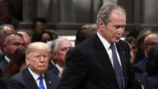 Former President George W. Bush walks past President Donald Trump to speak at the State Funeral for his father, former President George H.W. Bush, at the State Funeral at the National Cathedral, 5 December 2018, in Washington - Sputnik International