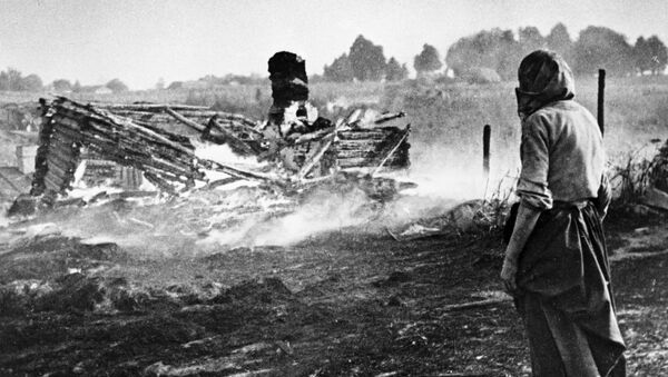 A woman stands next to a burnt house in a village during WW II - Sputnik International