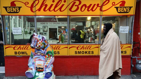 A member of the homeless community walks past Ben's Chili Bowl, whose founders Ben and Virginia Ali famously kept the restaurant running through very difficult times in the past, as the eatery navigates the coronavirus disease (COVID-19) outbreak with no seating, limited hours and help from a federal Payroll Protection Program Loan in Washington, U.S. April 30, 2020 - Sputnik International