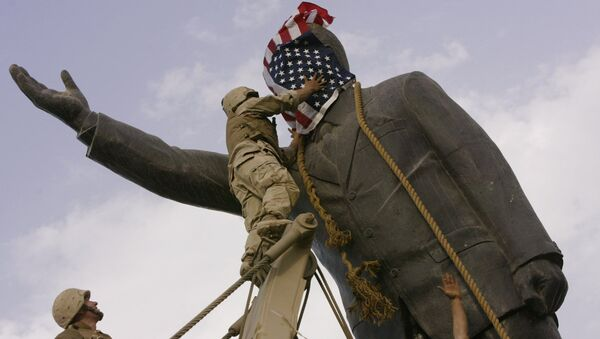 In this file photo taken Wednesday, April 9, 2003, an Iraqi man, bottom right, watches Cpl. Edward Chin of the 3rd Battalion, 4th Marines Regiment, cover the face of a statue of Saddam Hussein with an American flag before toppling the statue in downtown in Baghdad, Iraq. - Sputnik International