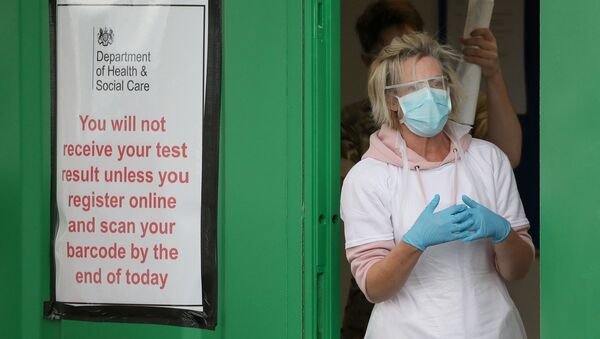 A staff member is pictured next to a banner at a COVID-19 testing centre amid the coronavirus disease outbreak, at Glasgow Airport, in Glasgow, Scotland April 29, 2020.  - Sputnik International