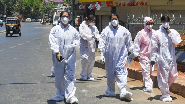 Healthcare workers wearing Personal Protective Equipment (PPE) walk out of a hospital during a government-imposed nationwide lockdown as a preventive measure against the COVID-19 coronavirus, in Mumbai on May 4, 2020. - Sputnik International