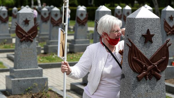 A woman mourns at a grave of a Russian soldier at the Olsany cemetery to commemorate the 75th anniversary of the end of World War Two in Prague, Czech Republic, May 8, 2020 - Sputnik International