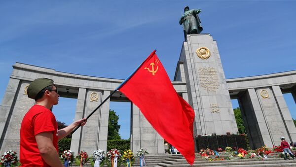 A man with a Soviet flag attends a celebration to mark Victory Day and the 75th anniversary of the end of World War Two at the Soviet War Memorial at Tiergarten Park in Berlin, Germany, May 8, 2020 - Sputnik International