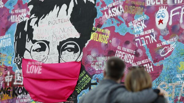 A couple look at the Lennon Wall with a face mask attached to the image of John Lennon, in Prague, Czech Republic, Monday, April 6, 2020.  - Sputnik International