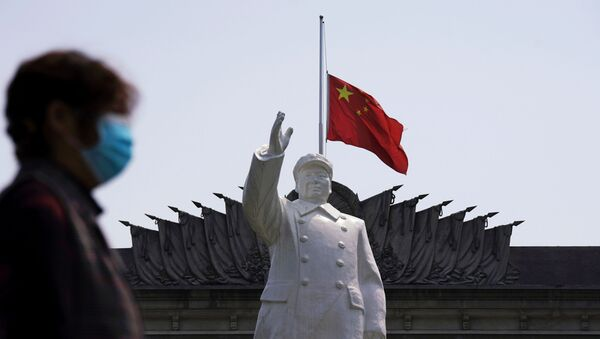 The Chinese national flag flies at half-mast behind a statue of late Chinese chairman Mao Zedong in Wuhan, Hubei province, as China holds a national mourning for those who died of the coronavirus disease (COVID-19), on the Qingming tomb-sweeping festival, April 4, 2020 - Sputnik International
