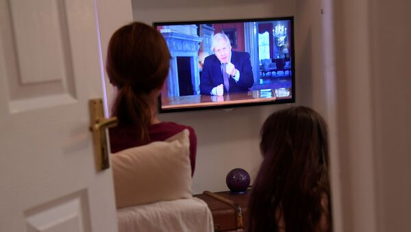 Family members in a house in London watch Britain's Prime Minister Boris Johnson on television during a broadcast to outline plans for gradually easing lockdown measures following the outbreak of the coronavirus disease (COVID-19), London, Britain, May 10, 2020   - Sputnik International