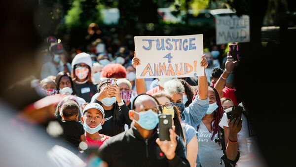 Supporters of the Georgia NAACP (National Association for the Advancement of Colored People) wearing protective masks protest after the death in February of Ahmaud Arbery, an unarmed young black man shot after being chased by a white former law enforcement officer and his son, at the Glynn County Courthouse in Brunswick, Georgia, U.S., May 8, 2020 - Sputnik International