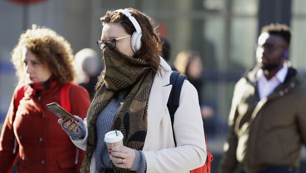 A commuter covers her face in London, Monday, March 16, 2020. For most people, the new coronavirus causes only mild or moderate symptoms, such as fever and cough. For some, especially older adults and people with existing health problems, it can cause more severe illness, including pneumonia. - Sputnik International