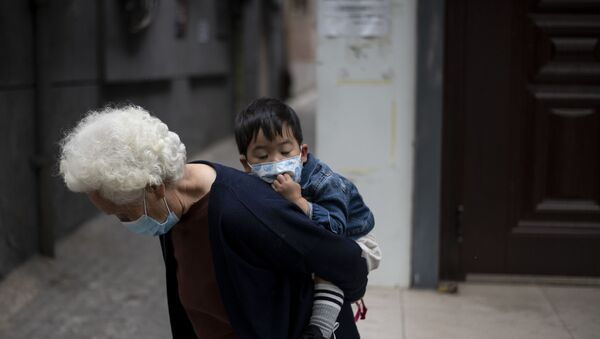 An elderly woman wearing a face mask piggybacks a boy along a street in  Beijing on May 11, 2020 - Sputnik International