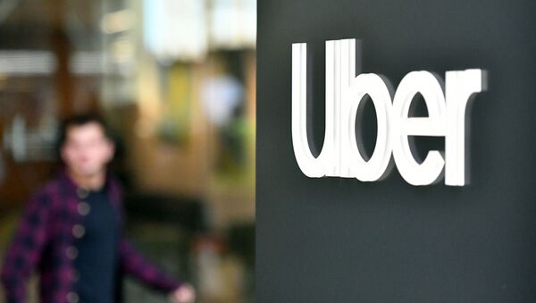 An Uber logo is seen on a sign outside the company's headquarters location as people protest nearby in San Francisco, California on May 8, 2019 - Sputnik International
