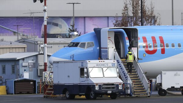 A worker walks up steps to the right of an avionics truck parked next to a Boeing 737 MAX 8 airplane being built for TUI Group at Boeing Co.'s Renton Assembly Plant Wednesday, March 13, 2019, in Renton, Wash - Sputnik International