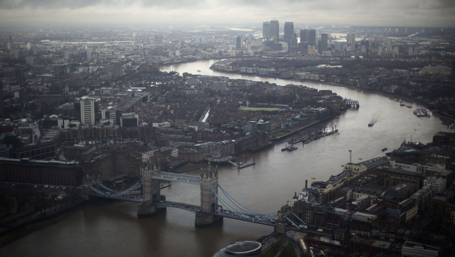 Tower Bridge, centre, and the Canary Wharf business district in the distance as the River Thames flows through London, are seen through a window during the official opening of The View viewing platform at the 95-storey Shard skyscraper in London, Friday, Feb. 1, 2013 - Sputnik International, 1920, 02.04.2021