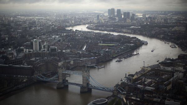 Tower Bridge, centre, and the Canary Wharf business district in the distance as the River Thames flows through London, are seen through a window during the official opening of The View viewing platform at the 95-storey Shard skyscraper in London, Friday, Feb. 1, 2013 - Sputnik International